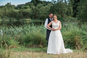 bride and groom at green valley near the small loch