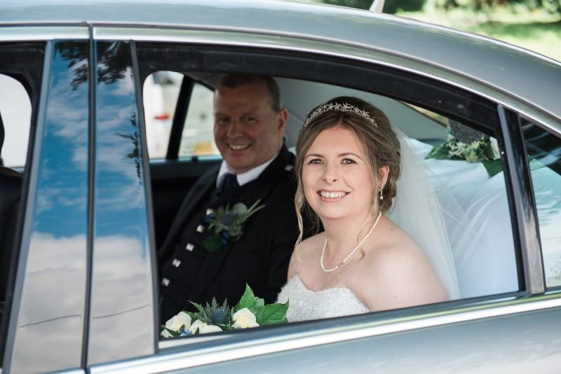 bride and dad in wedding car